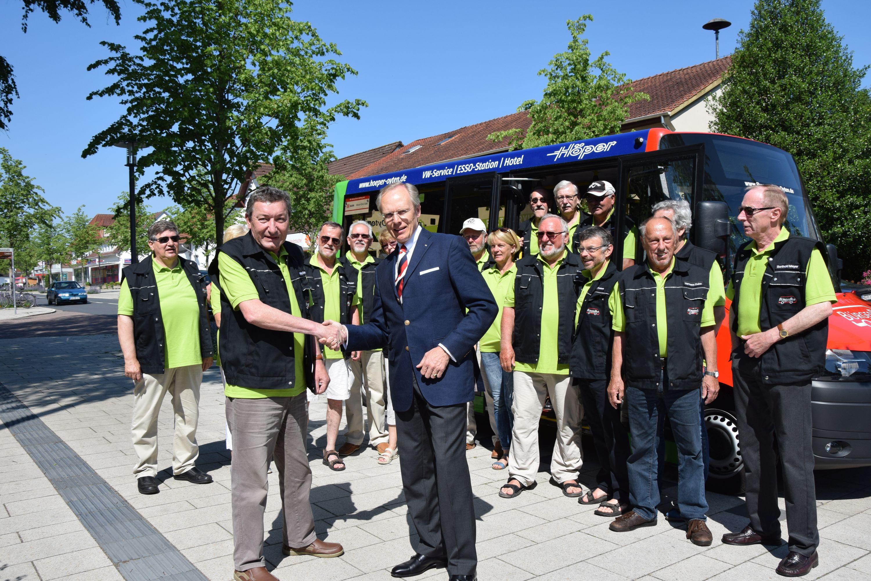 Maibaumübergabe durch den VdS Vorsitzenden Hans-Joachim Blohme (rechts) an den Vorsitzenden des Bürgerbusvereins Wolfgang Gabele. Im Hintergrund die Fahrerinnen und Fahrer vor dem Bürgerbus.